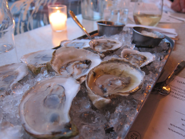oysters arranged on a bed of ice with a candle burning behind